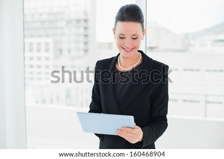Elegant businesswoman using tablet PC in a bright office - stock photo
