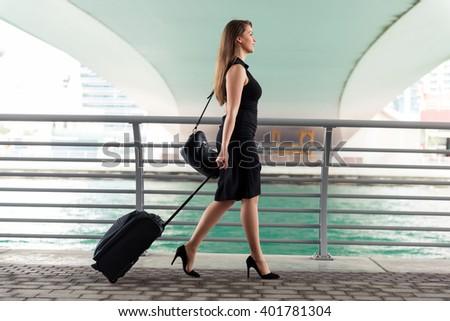 Elegant businesswoman with her luggage. - stock photo