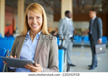 Elegant businesswoman with touchpad looking at camera on background of two men speaking - stock photo