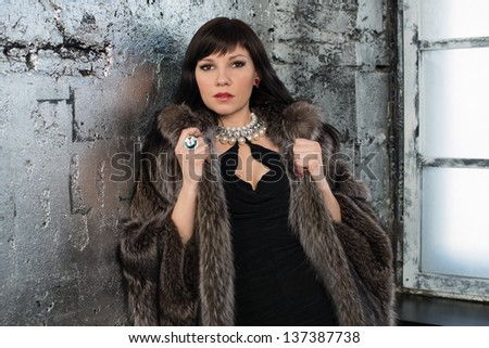 Elegant caucasian lady with long dark hair standing by the window and looking at camera. She is wearing fur coat and jewelry - stock photo