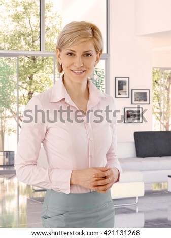 Elegant caucasian middle aged blonde businesswoman at home. Standing, smiling, looking at camera.