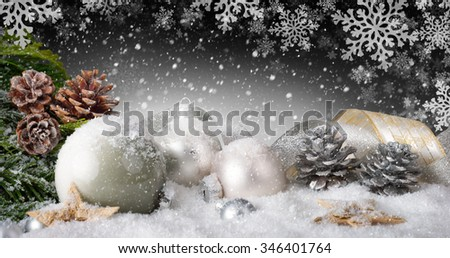 Elegant Christmas arrangement with baubles, nice ribbons, silver cones, lots of snow and ornamental large snowflakes in the dark gray background