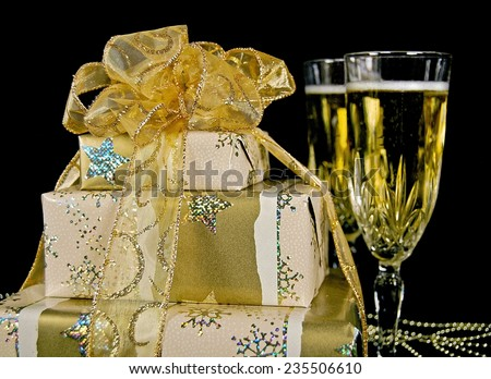 elegant Christmas gift with flutes of champagne and gold glittery bow on black - stock photo