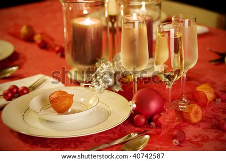 Elegant Christmas table setting in red and gold colors, with red Japanese lantern flower as focal point
