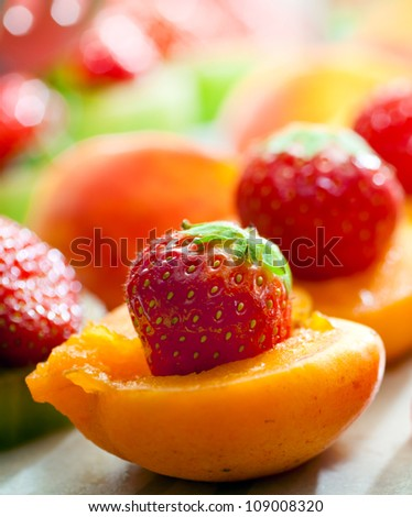 Elegant composition of apricots and strawberries - stock photo