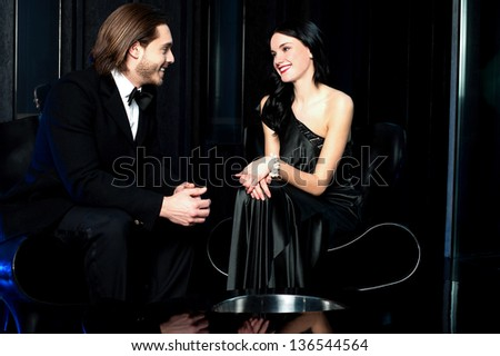 Elegant couple admiring each other, dark background. - stock photo