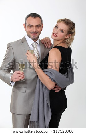 Elegant couple celebrating with champagne on white background