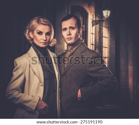 Elegant couple in autumnal coats standing outdoors at night - stock photo