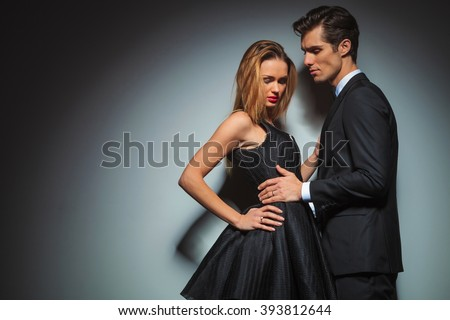 elegant couple in black posing together in black studio background. Man with hands on woman waist  is looking away while woman with hand on waist is looking down - stock photo