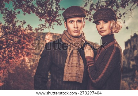 Elegant couple in caps against autumnal landscape - stock photo