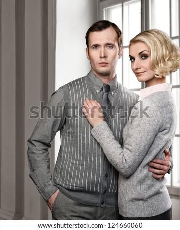 Elegant couple indoors standing near window - stock photo