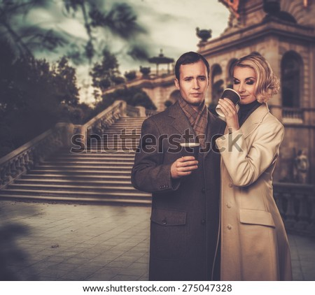 Elegant couple outdoors with cups of hot drink - stock photo