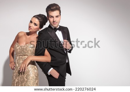 Elegant couple posing while holding arms, both looking at the camera. - stock photo