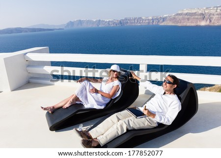 Elegant couple resting on the deck chair at the seaside terrace