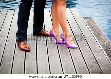 Elegant couple's legs on wooden pier - stock photo
