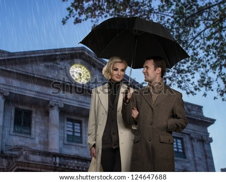 Elegant couple with umbrella against building facade - stock photo