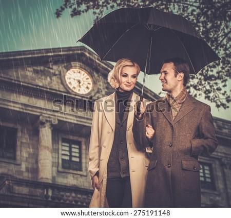 Elegant couple with umbrella against building facade - stock photo