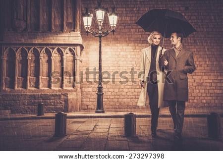 Elegant couple with umbrella walking outdoors in the rain - stock photo