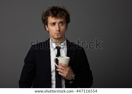 elegant curly men in suit holding a cup of coffee or tea in hands, on gray background