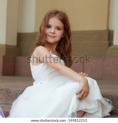 Elegant cute little girl in a white dress with beautiful hair in sneakers on Beauty and Fashion