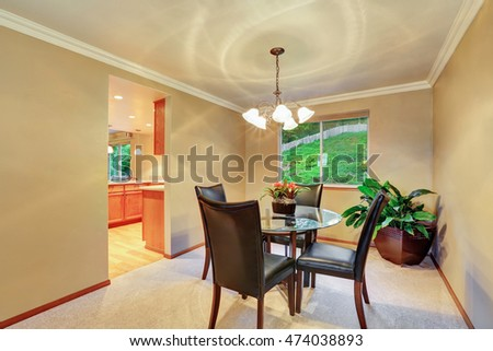 Elegant dining room interior with plant pot in the corner. Modern glass table with black leather chairs. Northwest, USA