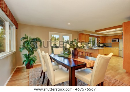 Elegant dining room with fresh flowers on the table. Kitchen view in the background. Northwest, USA