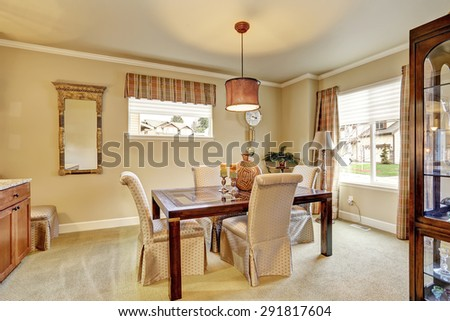 Elegant dinning room with carpet, table, and chairs.