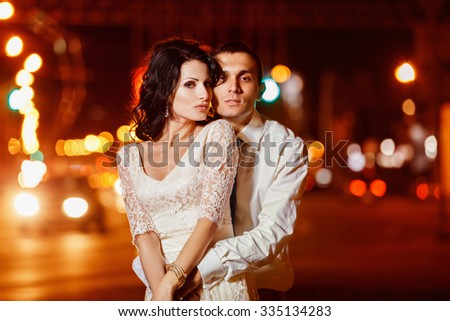 Elegant dressed man is tenderly embracing beautiful woman at bright night street lights background.