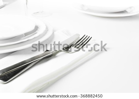 Elegant empty plate, cutlery, napkin and glass on white. Selective focus.