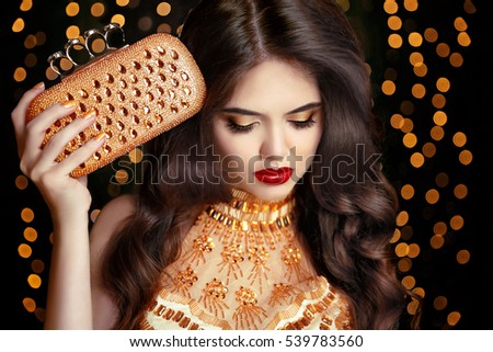 Elegant fashion brunette woman in gold. Wavy hair style. Red lips Makeup. Healthy shiny hairstyle. Sexy girl model in golden dress with trendy clutch bag Accessories over bokeh lights background.