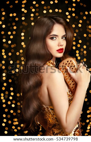 Elegant fashion brunette woman. Wavy hair style. Red lips Makeup. Healthy shiny hairstyle. Sexy girl model in golden dress with trendy clutch bag Accessories over bokeh lights background.