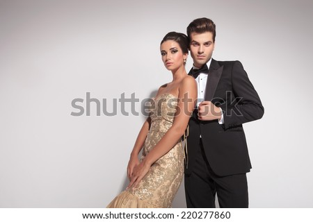 Elegant fashion couple posing against grey background, both looking at the camera. - stock photo