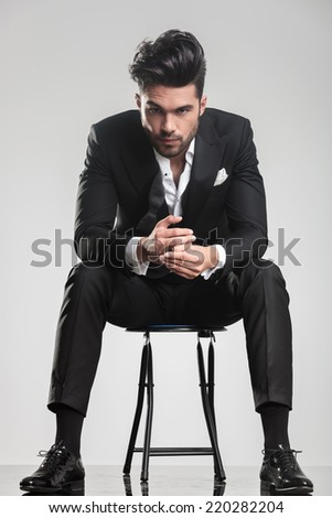 Elegant fashion man in tuxedo looking at the camera while sitting on a stool, holding his hands. - stock photo