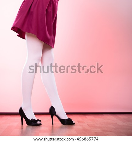 Elegant fashion outfit. Fashionable woman long legs in white color pantyhose black shoes