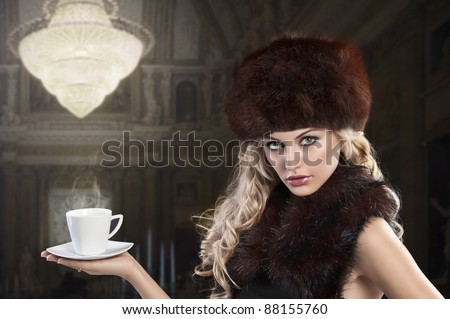 elegant fashion shot of a long haired blonde holding a hot cup of tea and wearing a fur stole and a huge brown fur hat - stock photo