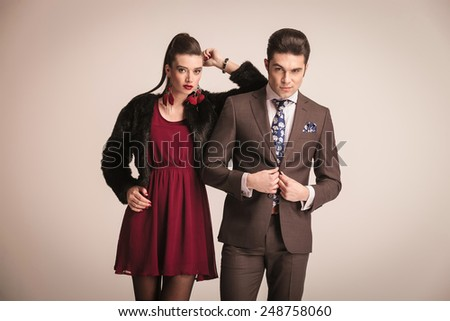 Elegant fashion woman leaning on her lover while he is closing his jacket.