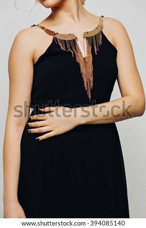 elegant fashionable black dress with gold jewelry on a beautiful young blonde girl fashion model with curly long blond hair chic luxury manicure on nails isolated on white background - stock photo