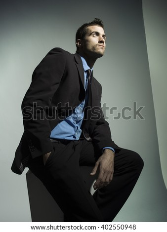 elegant fashionable man with black suit in grey background - stock photo