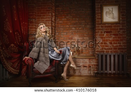 Elegant fashionable woman wearing fur cape in a dark vintage interior