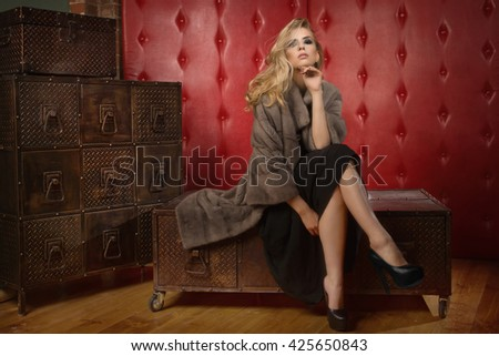 Elegant fashionable woman wearing fur cape in a dark vintage interior. Shoes is no trademark