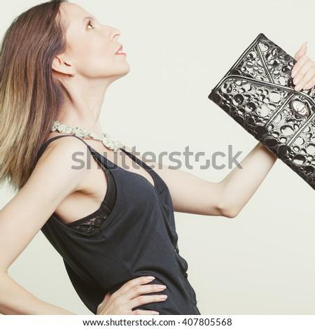 Elegant fashionable woman with leather handbag. Stylish girl holding black bag. Female fashion vogue. Studio. Side profile view. - stock photo