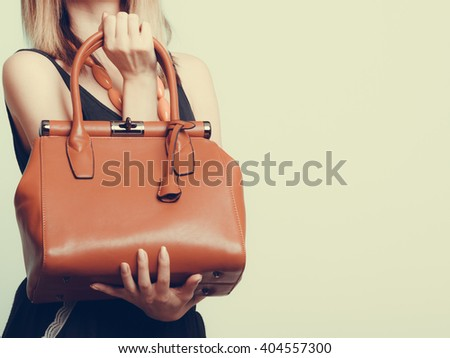 Elegant fashionable woman with leather handbag. Stylish girl holding brown bag. Female fashion vogue. Studio. Instagram filter. - stock photo