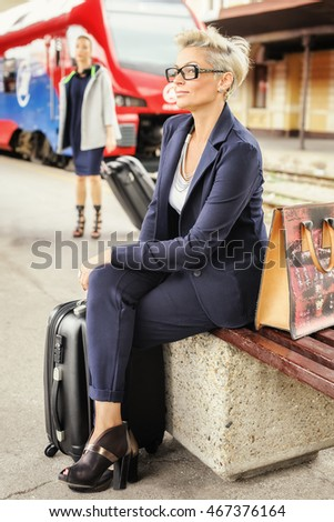 Elegant fashionable woman with suitcase standing and posing on the railway station. Travel, trip, journey