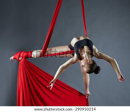 Elegant female dance posing on aerial silks - stock photo