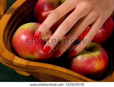 Elegant female hand picking apple from wooden basket.