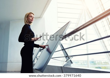 Elegant female holding mobile phone while standing front high tech digital device in office interior, young female thinking while searching information on cell telephone and interactive display - stock photo