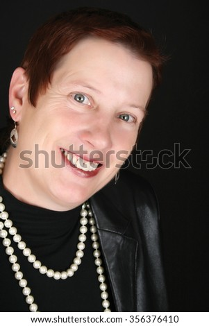 Elegant female wearing a black leather jacket and pearls - stock photo
