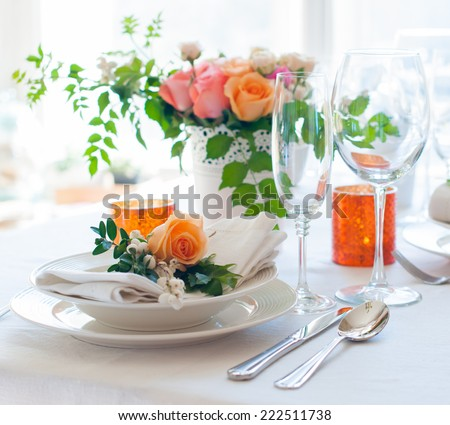 Elegant festive table setting with colorful flowers, cutlery, candles. Wedding table decoration. - stock photo