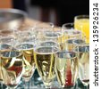 Elegant flutes filled with champagne or sparkling white wine for celebrating the toasts and speeches at a wedding or festive function - stock photo