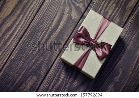 elegant gift box on a wooden background - stock photo